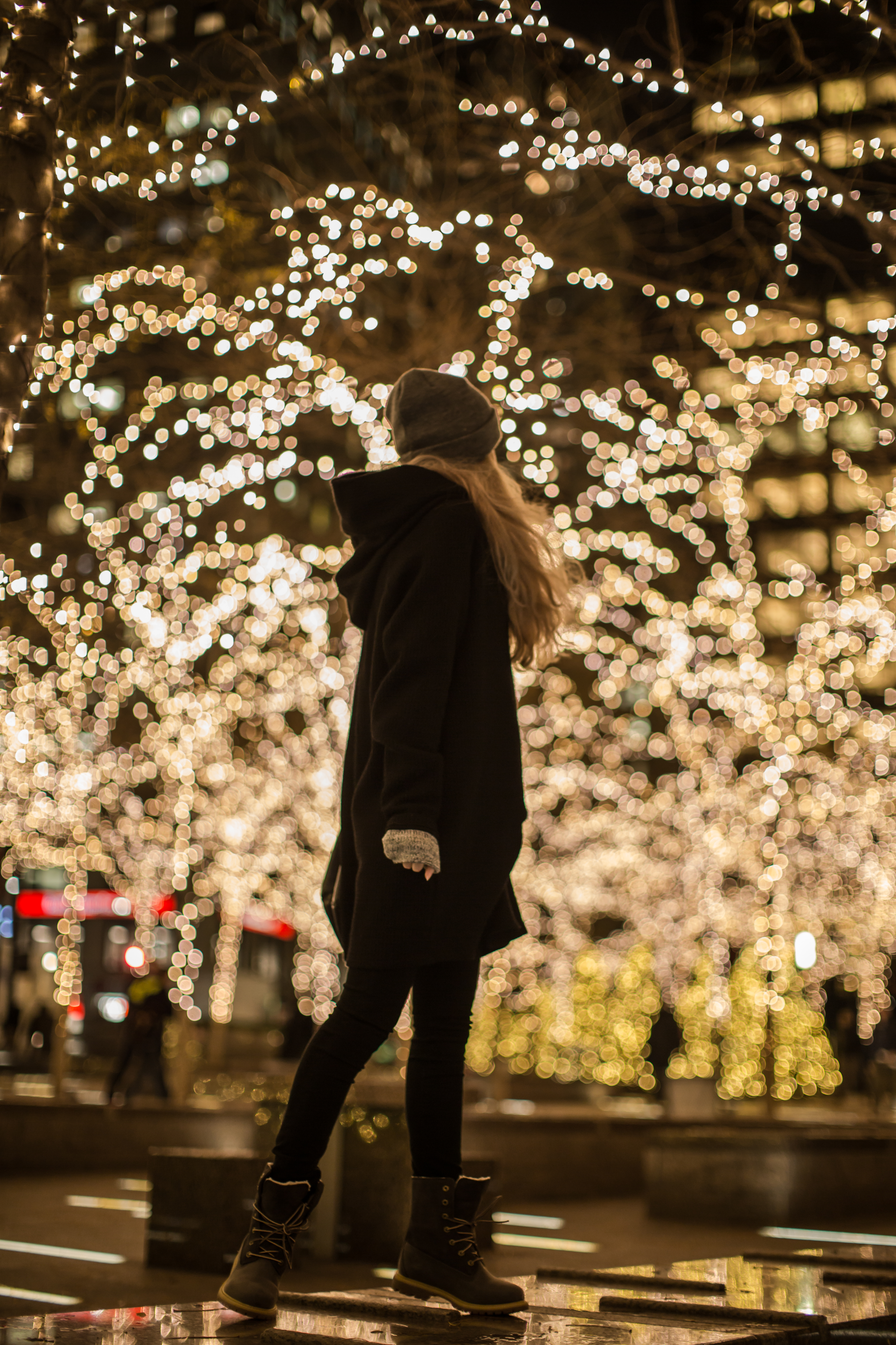 Girl standing on the blurred christmas lights background example image 1