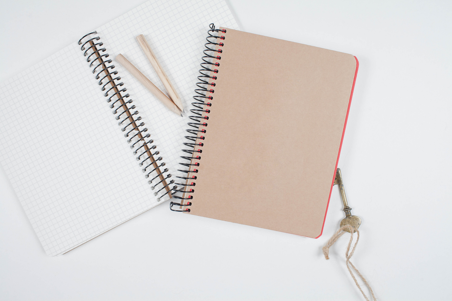 Old notebooks and pencils, key on white table example image 1