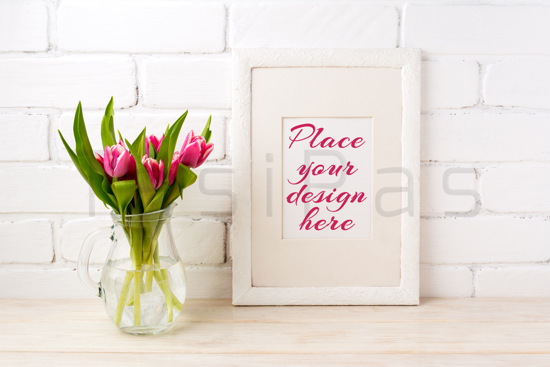 White frame mockup with magenta pink tulips bouquet in glass jug near white painted brick wall.  example image 1