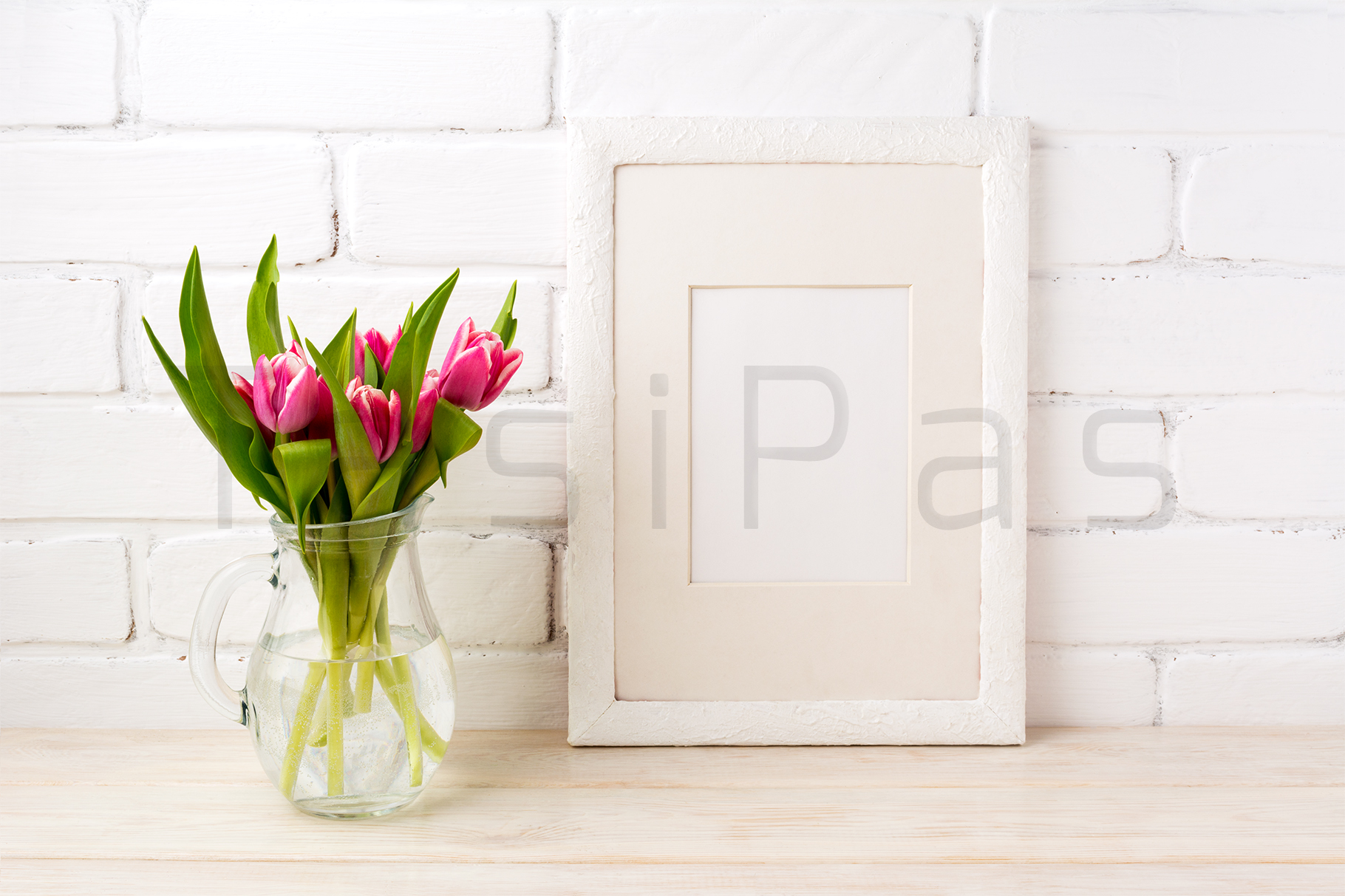 White frame mockup with magenta pink tulips bouquet in glass jug near white painted brick wall.  example image 2