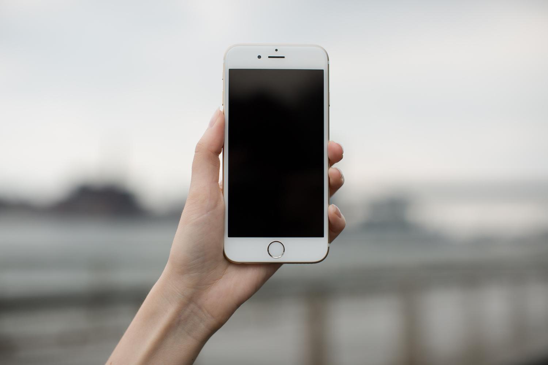 Female hand holding iPhone 8 ,blur river whit bridge on background example image 1