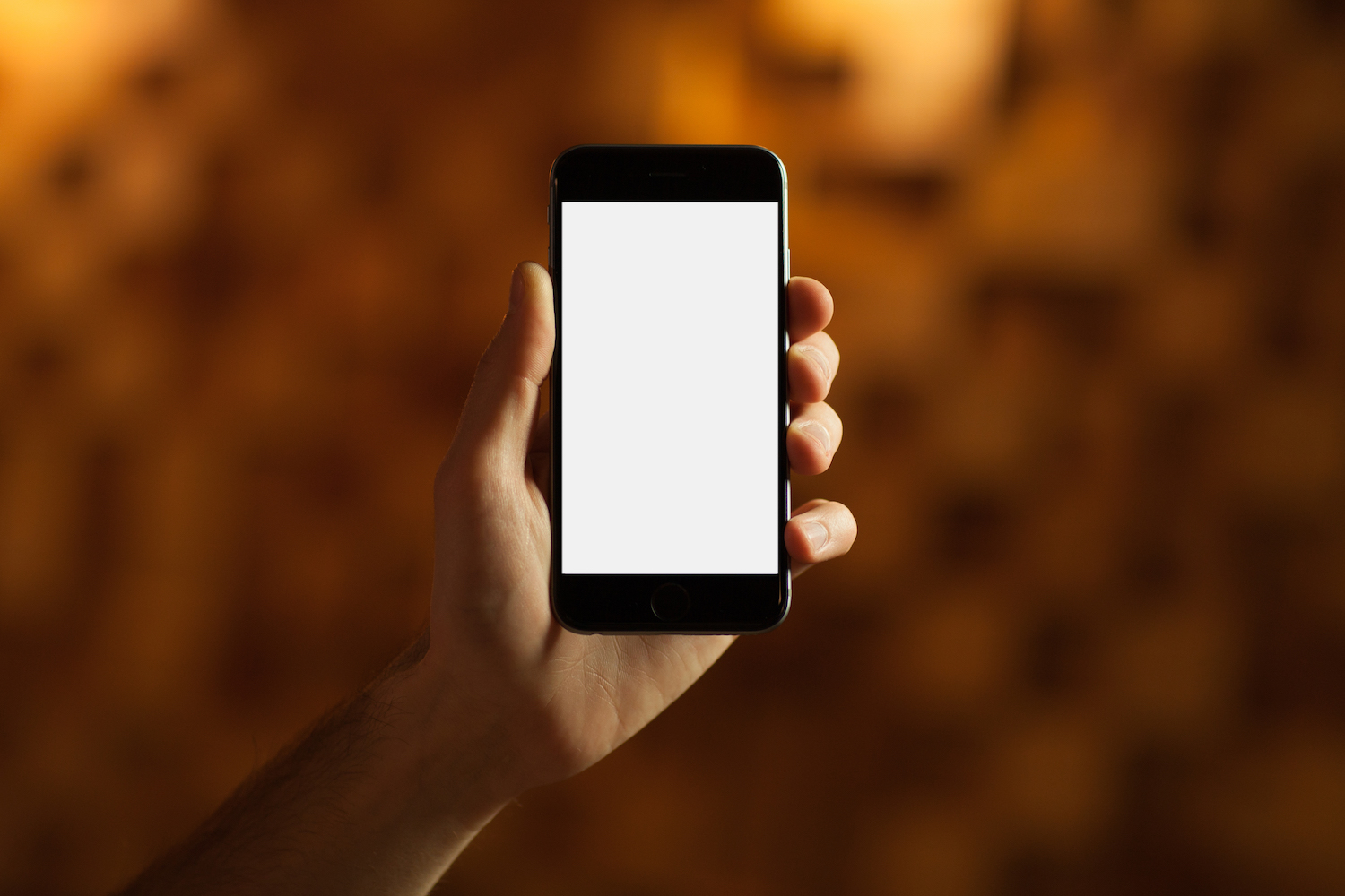 Male hand holding smartphone with blank screen on wood background example image 1