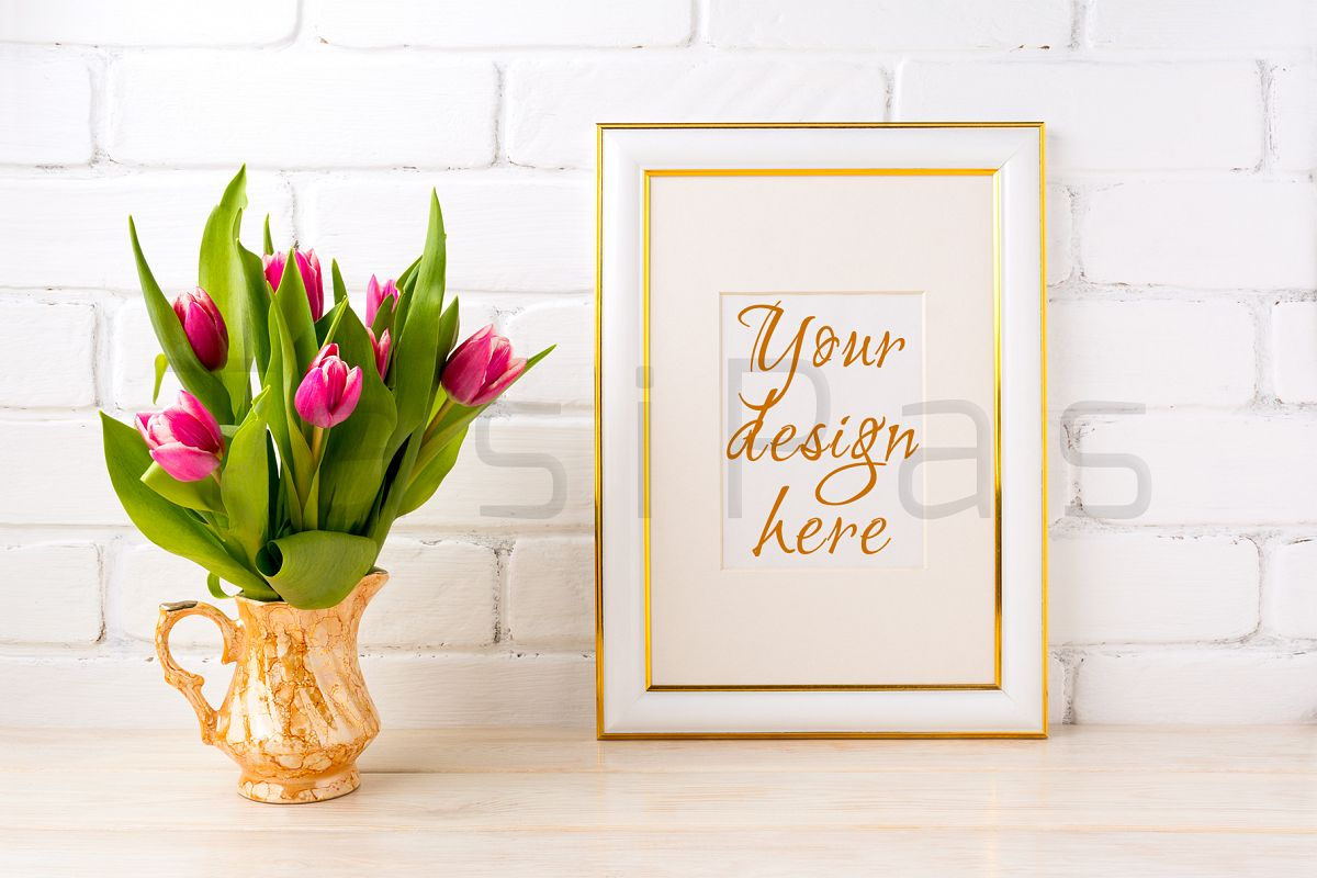 Gold decorated frame mockup with bright pink tulips bouquet in gold jug near white painted brick wall.  example image 1