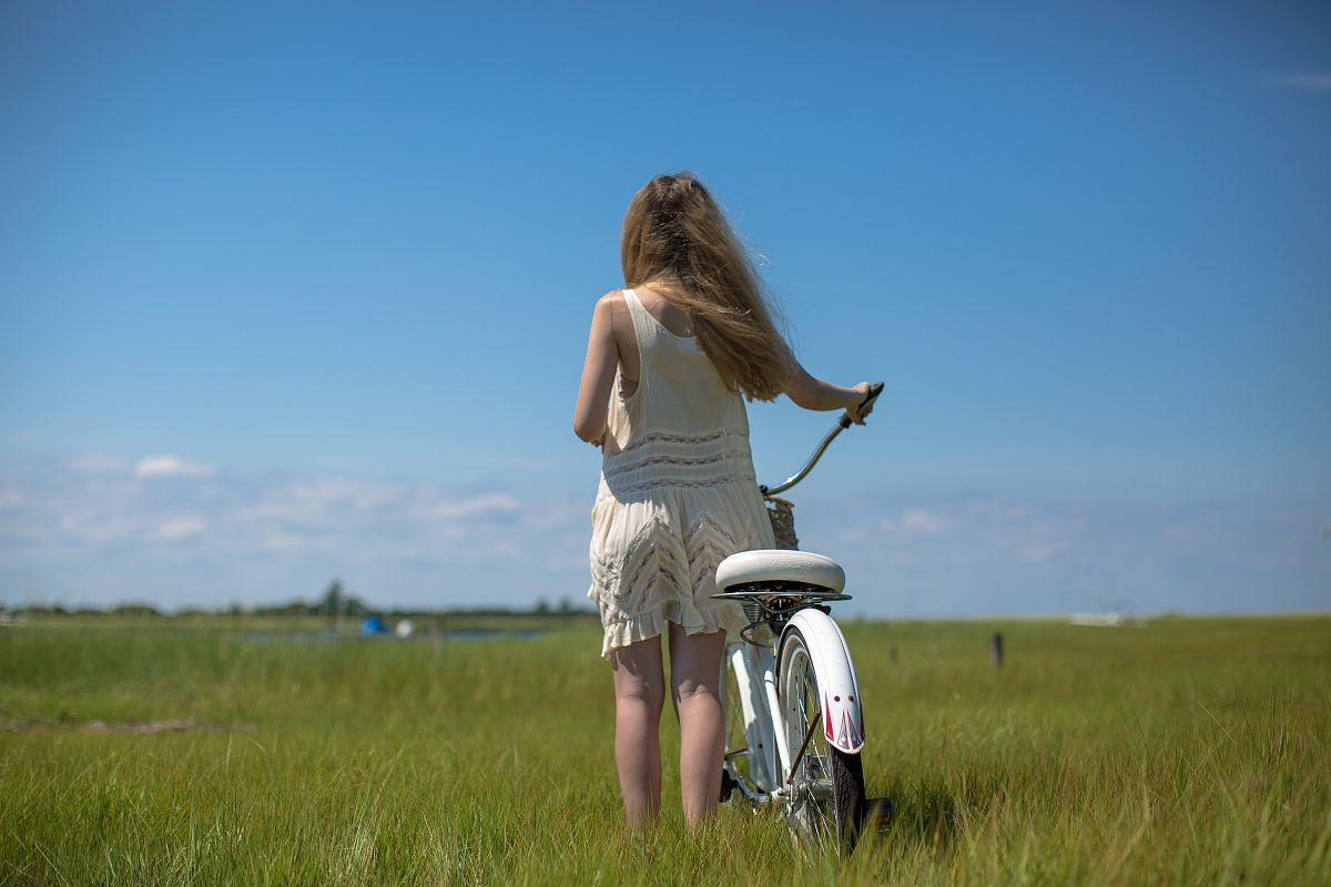 Women with a bike on the green field example image 1