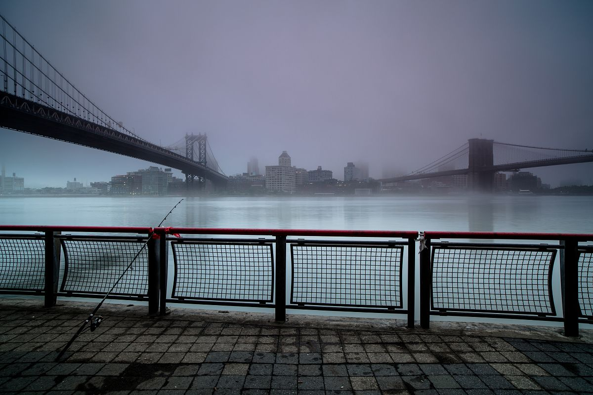 Foggy morning at the pier in Manhattan ,with fishing rod on a pier	 example image 1