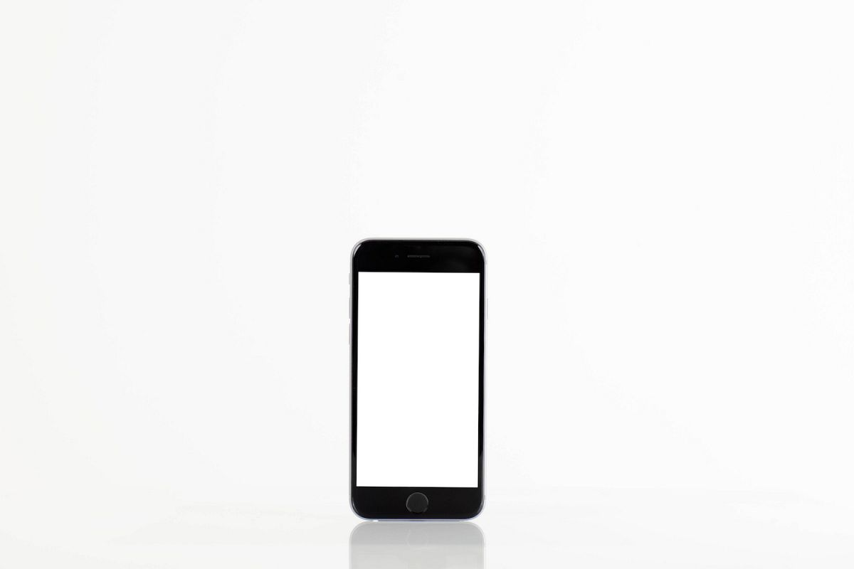 Standing mobile smart phone with blank screen on white background