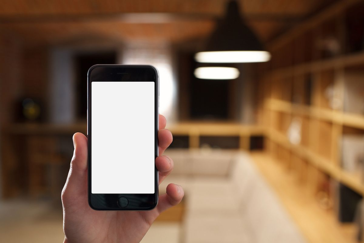 Hand holding mobile smart phone with blank screen in office example image 1