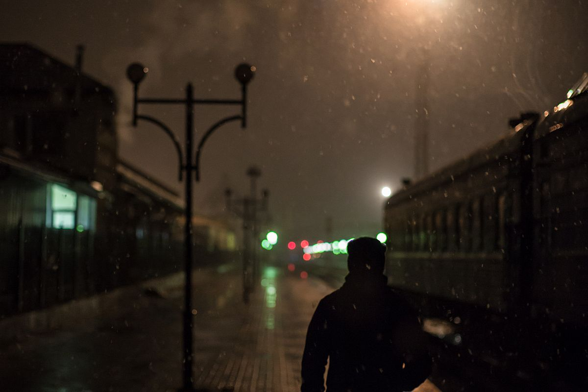 Man on a train station at night	 example image 1