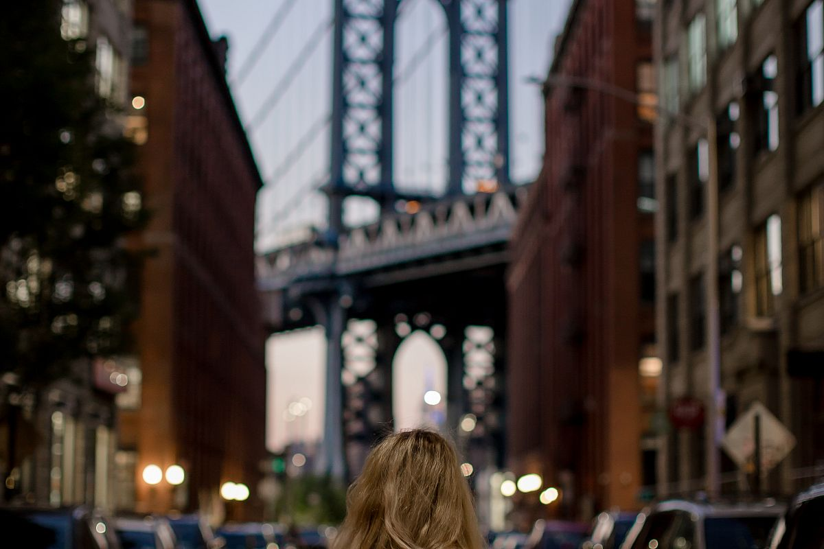 Lady standing on old street, looking at manhattan bridge	 example image 1