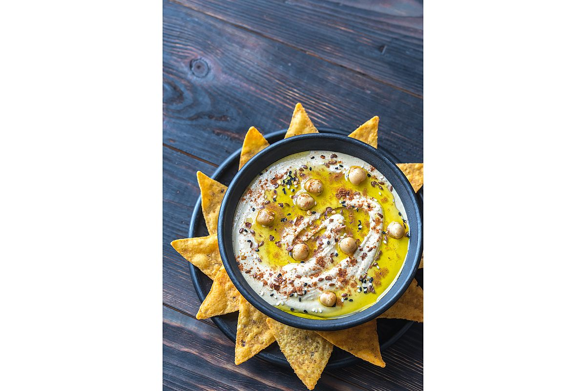 Bowl of hummus with tortilla chips example image 1