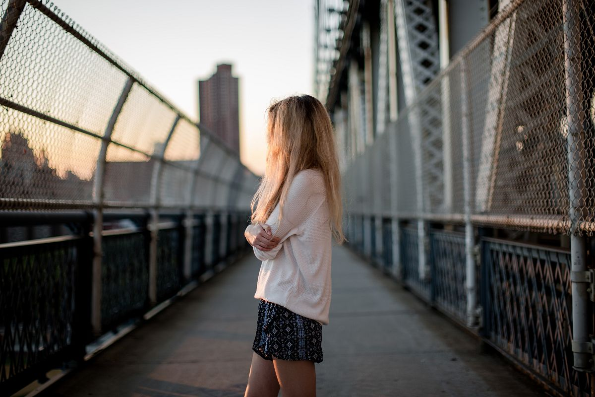 Girl standing on a bridge at sunset	 example image 1