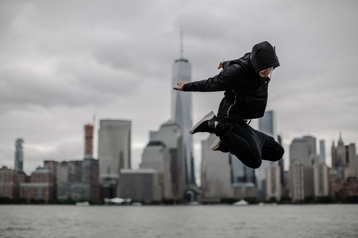 Man jumping on the front of downtown manhattan view example image 1