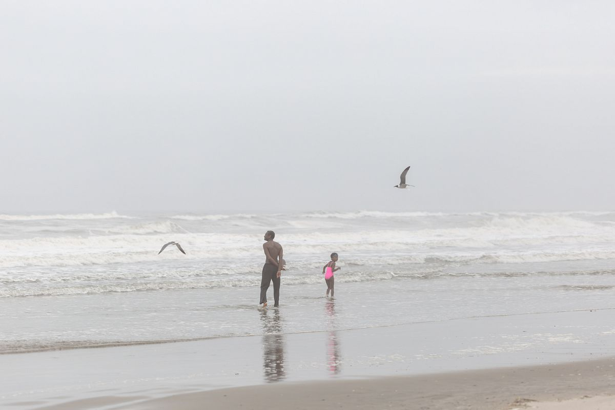 Man with child in the ocean on a foggy day example image 1