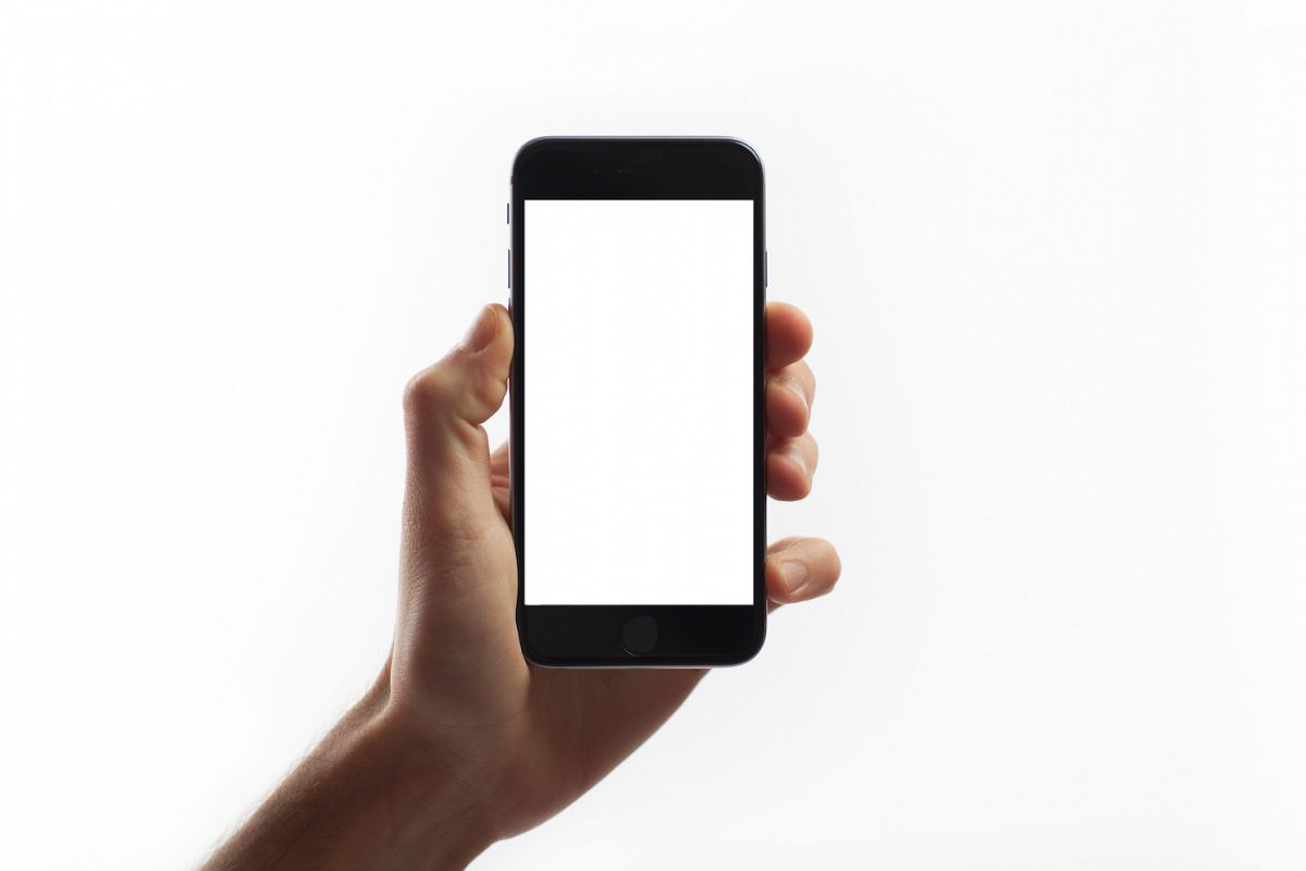 Hand holding mobile smart phone with blank screen example image 1