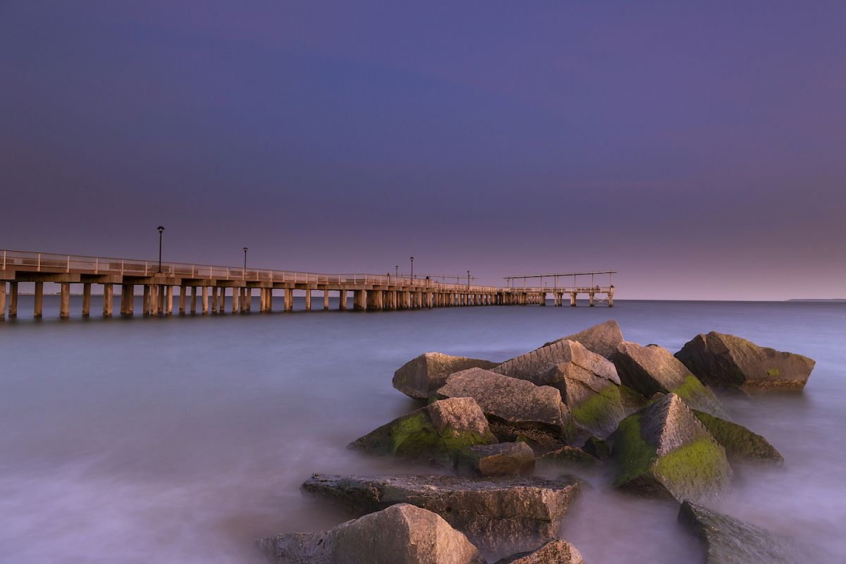 View on the pier in ocean from the rocky beach at sunset wit example image 1