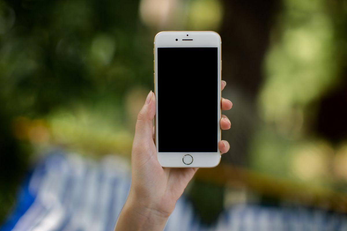 Female hand holding smart phone outside example image 1