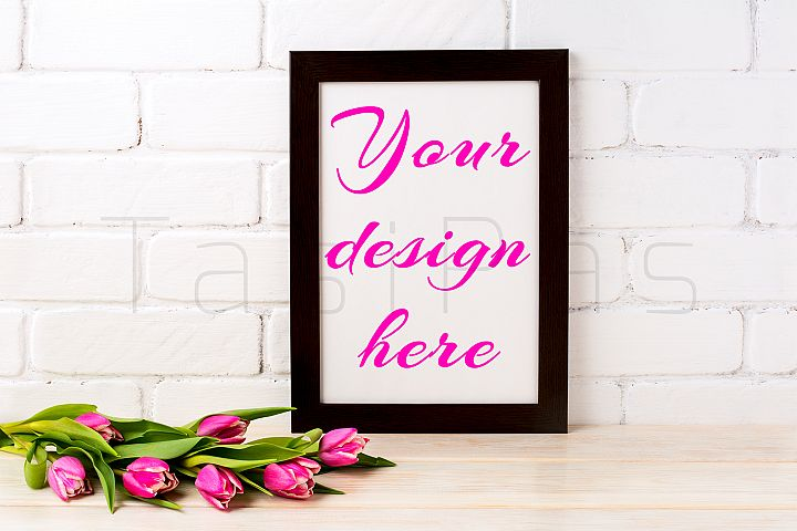 Black brown  frame mockup with rich magenta pink tulips bouquet near painted brick wall.