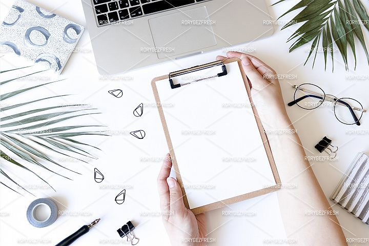 Home office desk with laptop, glasses, stationery, notepads, green leaves. Girl hands hold a clip board on a white background