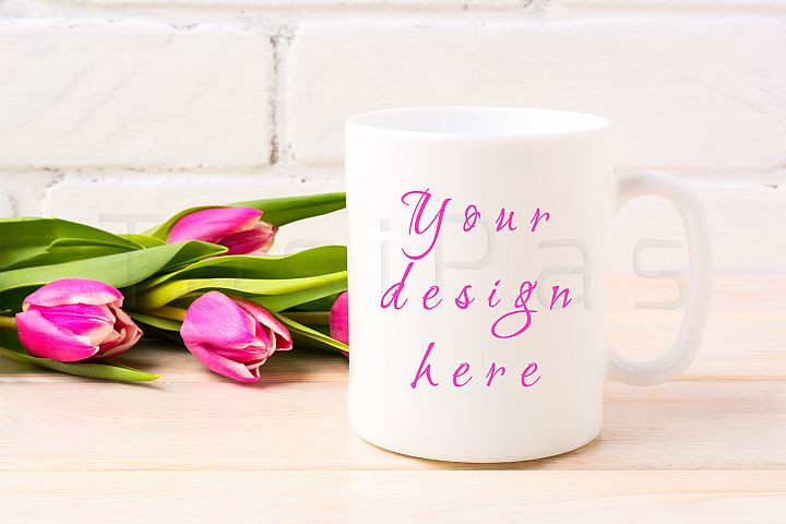 White coffee mug mockup with rich magenta pink tulips bouquet near painted brick wall.