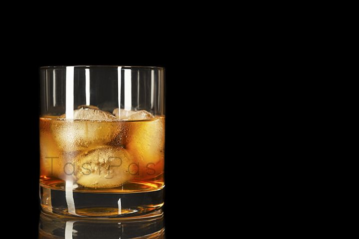 Bourbon glass on the black background, copy space.