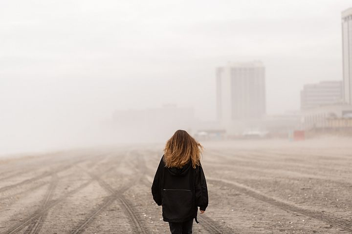 Girl on walking on the beach during fog at atlantic city