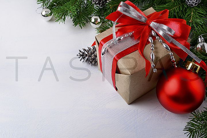 Christmas silver beads decorated gift box with red ribbon.