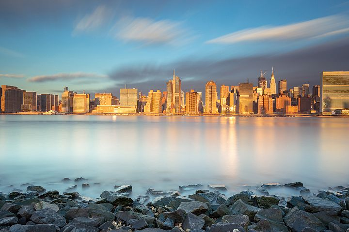 Midtown Manhattan view from east river beach at sunrise
