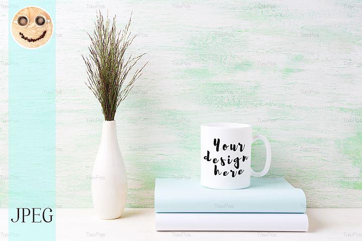 White coffee mug mockup with dark meadow grass in vase
