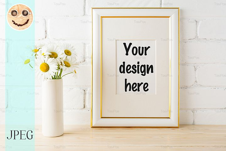 Gold decorated frame mockup with daisy near painted brick wa