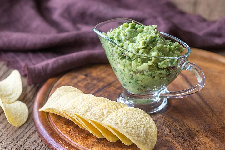 Guacamole with chips on the wooden board