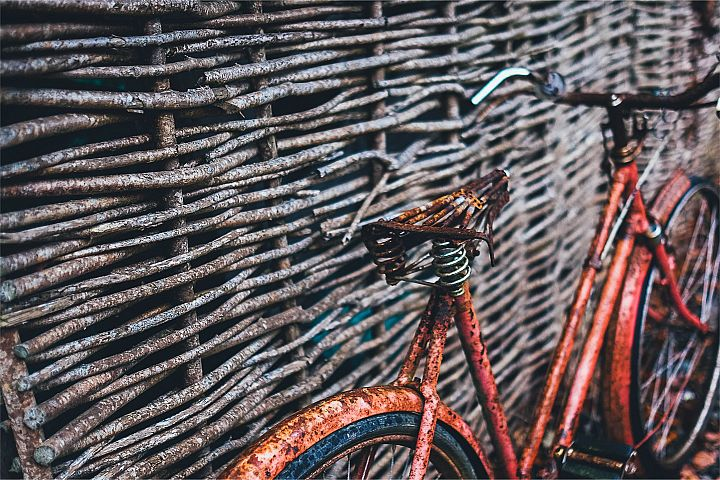 red bicycle parked beside brown wood wall at daytime