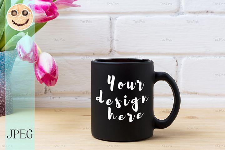 Black coffee mug mockup with magenta tulip