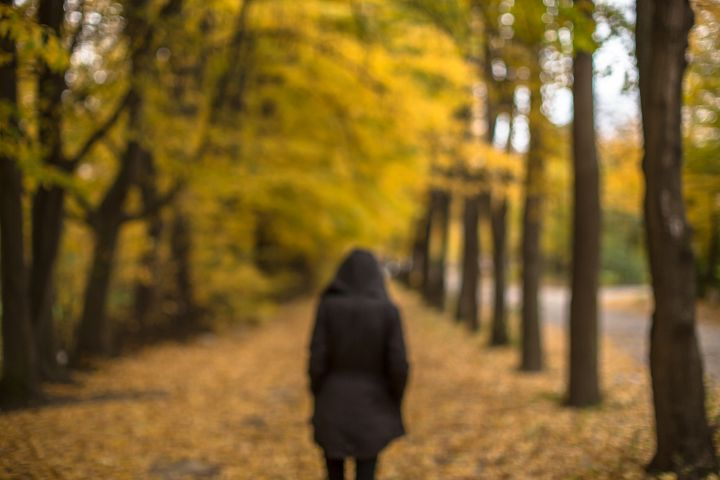 Blurred walking girl on a autumn alley