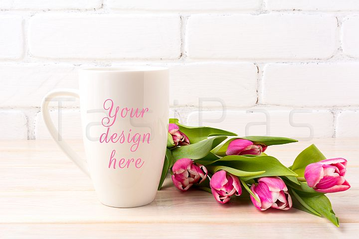 White coffee latte mug mockup with bright pink tulips bouquet near painted brick wall.