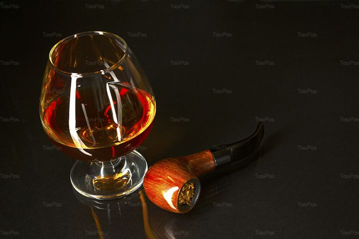 Whiskey glass and smoking pipe on black background