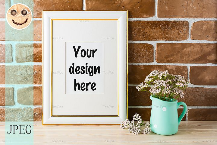 Gold decorated frame mockup soft pink flowers, brick wall