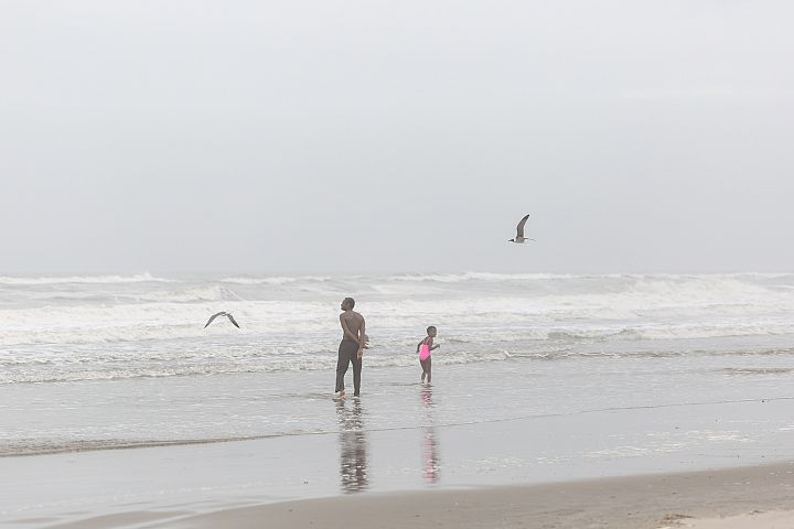 Man with child in the ocean on a foggy day
