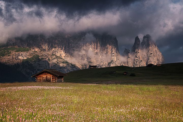 Cottages in a dramatic scene in Dolomites