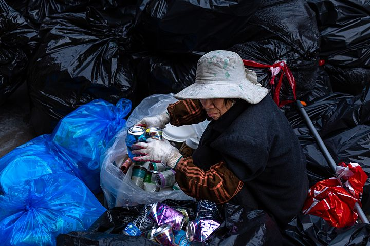 Chinese older woman collecting cans from trash