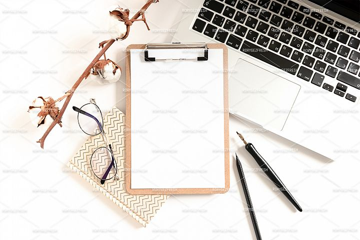 Workspace with clipboard mockup, laptop, glasses, notepads