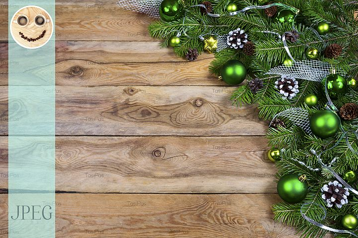 Christmas garland with green baubles on the wooden backgroun