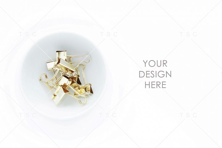 Gold Paper Clips on a White Bowl Stock Photo