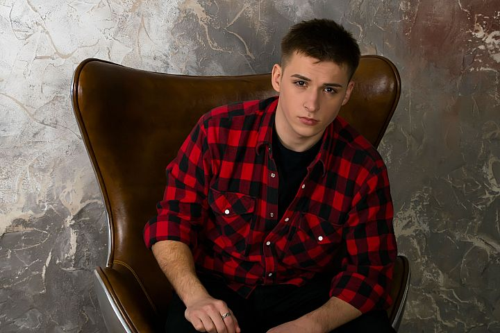 A young man in a hipster shirt sits in a beautiful chair