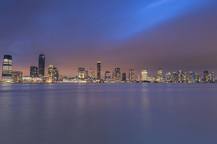 Jersey City skyscraper view at night from Hudson river a