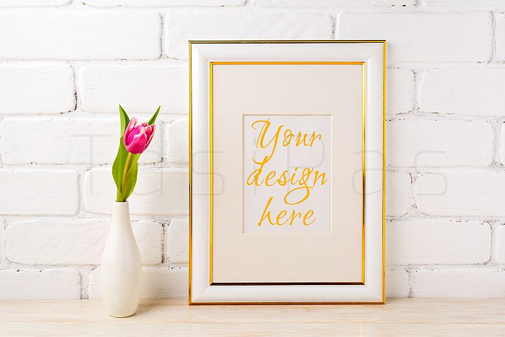 Gold decorated frame mockup with rich magenta pink tulip in elegant vase near white painted brick wall.