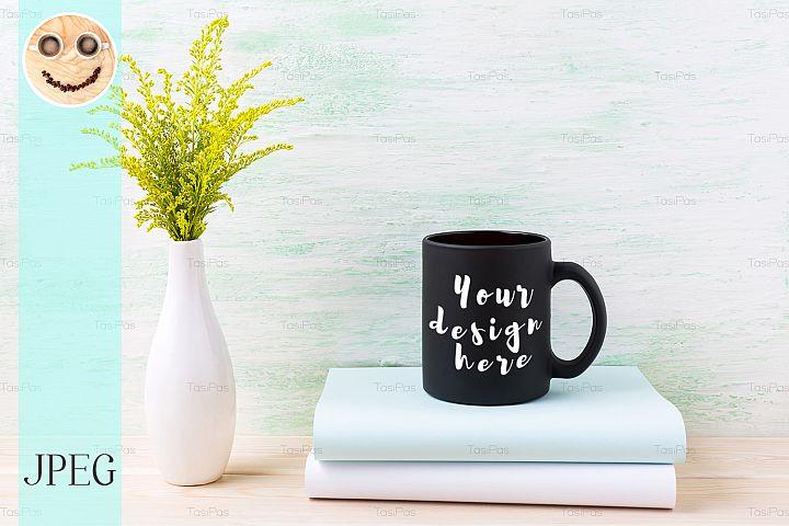 Black coffee mug mockup with ornamental green grass and book