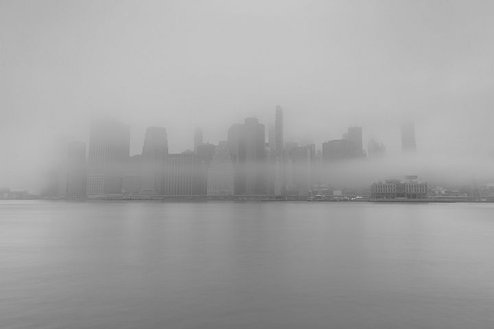 Financial district covered in fog from east river in black a